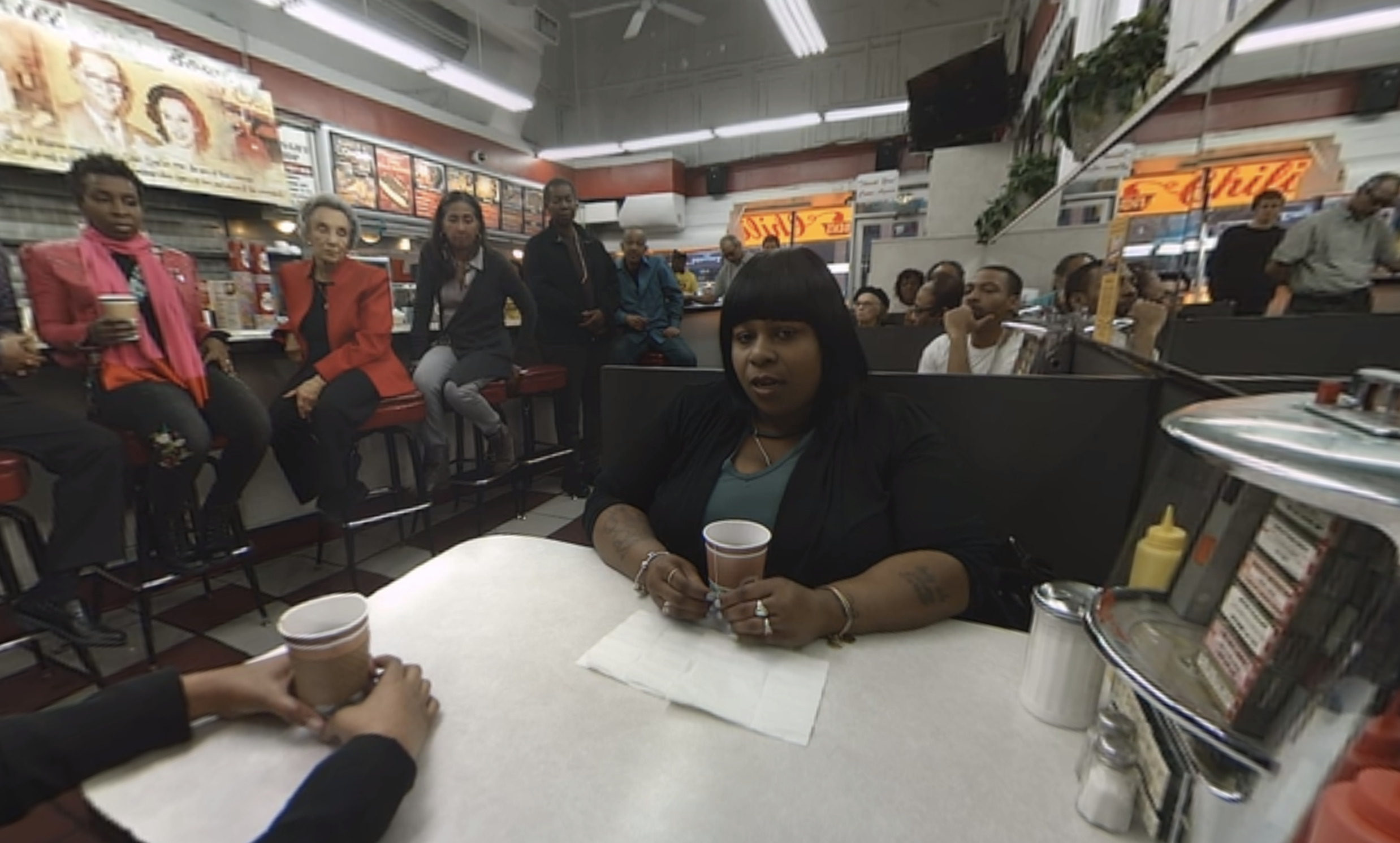 Photo of Samaria Rice talking about losing her son, Tamir, inside Ben's Chili Bowl in the VR documentary Traveling While Black.